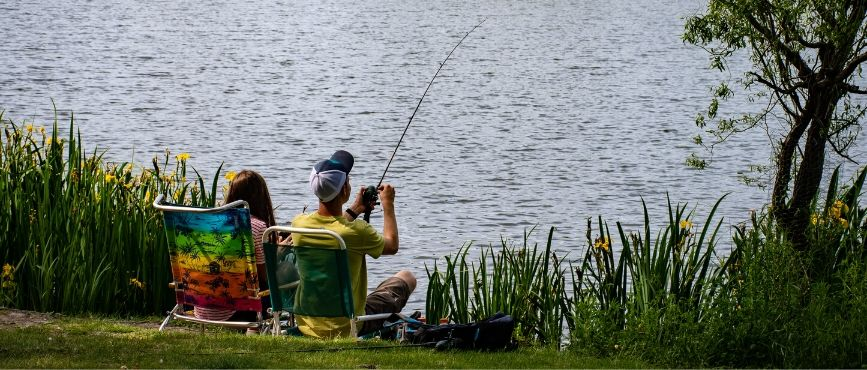 two people fishing from a grassy shore