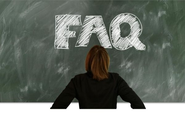 woman looking at writing on a chalkboard that says FAQ